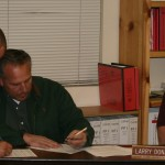 Firefighter Adam Rodriguez (left) and Administrative Captain Mark LaMont sign the letter of understanding between the Career Firefighters Asssociation and IFPD as Commission Larry Donahoo, who had already signed, watches