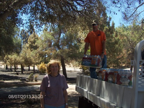 Edwina Scott, executive director Mountain Communities Fire Safe Council, Twin Pines resident, survived the Silver Fire. Pete Coy, PCWD, helps her with the water delivery