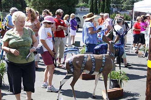 Dozens of people came out to view the painted deers at Forest Lumber Sunday, the only time all 22 deer sculptures were to be together. The Art Alliance of Idyllwild, which has organized this pubic art display, will distribute each sculpture to its personal location throughout town this week.  Photos by Jenny Kirchner