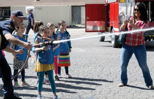 Idyllwild Firefighter Adam Rodriguez teaches a group of Girl Scouts how to aim and properly operate the fire hose Saturday afternoon during IFPD's open house. The kids had to knock over a basketball that was balancing on traffic safety cones.