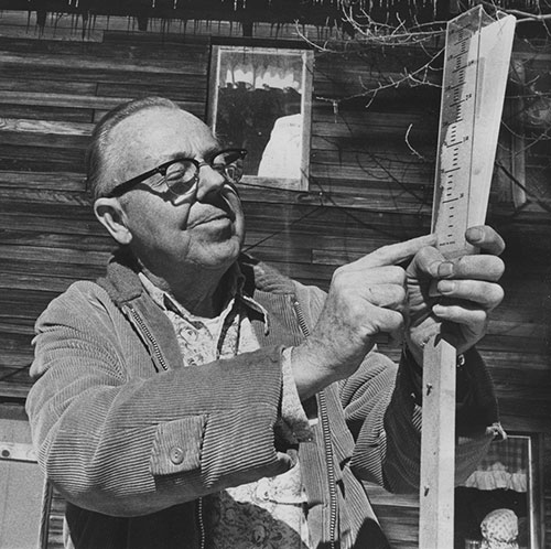The late Bob Gray with his precipitation gauge. For many years, Bob recorded temperature, rain and snow faithfully and conscientiously.  He was the town's best weather prophet. File Photo
