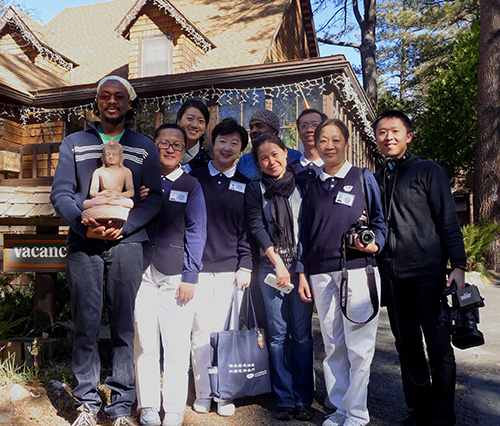 Rodney Williams (left, holding Buddha) and Ian Scott (rear with cap), owners of the Strawberry Creek Inn B&B, were visited by the Buddhist Tzu Chi Foundation of San Dimas, Monday, Jan. 6. They had learned about the Buddha's theft and came to present Buddha' to Williams, Scott and another.           Photo by Holly Owens