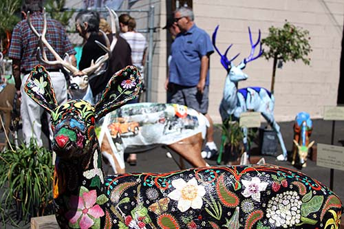 Dozens of people came out to view the painted deers at Forest Lumber Sunday, Sept. 15, the only time all 22 deer sculptures were to be together. The Art Alliance of Idyllwild, which organized this pubic art display, distributed each sculpture to its personal location throughout town that week.    		Photo by Jenny Kirchner