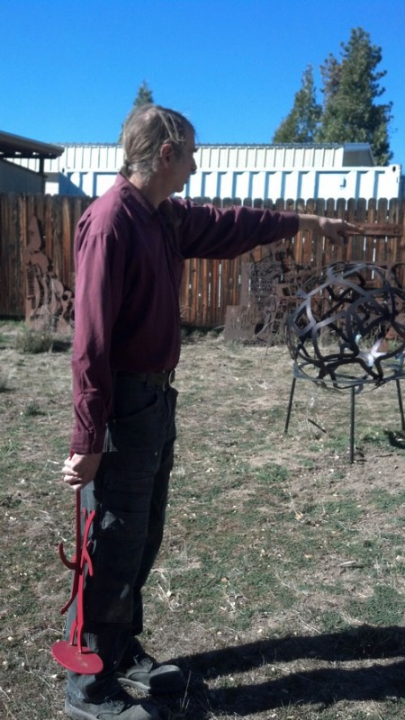 "Dore Capitani points to one of his many metal sculptures in his Art Garden. ""It's heaven here. I'm the happiest man on the Hill,"" said Capitani.    Photo by Jay Pentrack"