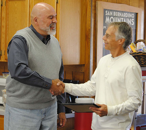 Pine Cove Water District President Mike Esnard (left) presents a certificate of appreciation to Robin Oates of Robin Oates Real Estate for his help representing PCWD in its recent property purchase. Photo by J.P. Crumrine