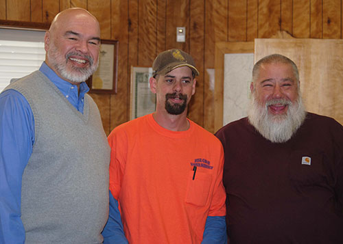 Jeremy Potter (center), maintenance worker, receives recognition for 10 years of service without a day of sick leave from Pine Cove Water District President Mike Esnard (left) and General Manager Jerry Holldber (right). Photo by J.P. Crumrine
