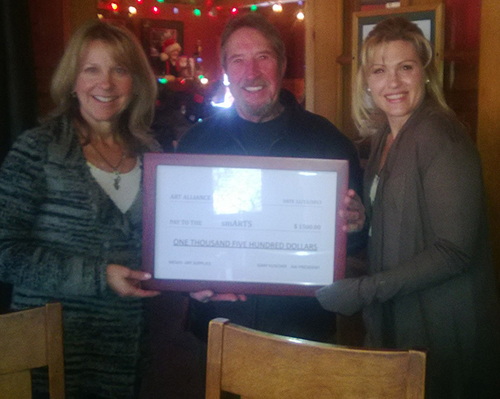 At left, on Dec. 13, Gary Kuscher (center), president of the Art Alliance of Idyllwild, presented a $1,500 check from AAI to members of the smARTS Committee Joann Tomsche (left) and Heather Mello (right) at Café Aroma. AAI helps support visual arts and the smARTS program, which provided more than 220 classes to Idyllwild School students last year.     Photo by Mallory Cremin