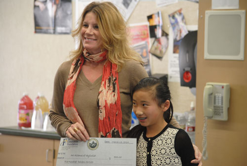 Meixing Hunt-Babcock (right), Idyllwild School sixth-grader, presents a check for $500 from the Idyllwild School Youth Grantmakers to Kirsten Ingbretsen, secretary of the Art Alliance of Idyllwild. The committee awarded the funds to the AAI for its Summer Sizzling Arts program for middle school students.          Photos by J.P. Crumrine