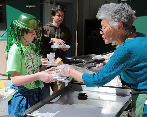 """Dustin Ledbetter (left), 12, receives a burger from """"Grandma Neu"""" on St. Paddy's Day during the barbecue lunch at Idyllwild School.                                                     Photo by Jenny Kirchner"""