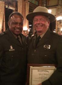 Robert Peek (right) holds his Award of Valor which he received for saving Idyllwild resident Paul Colucci's life last year. Congratulating Peek is Retired Major General Anthony Jackson, the current director of California's State Parks. Photo courtesy of Judith Way