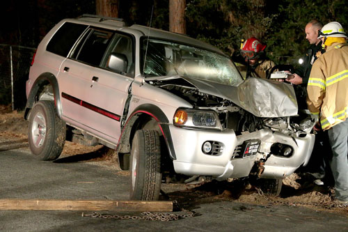 According to California Highway Patrol Officer Mike Murawski (center), at least two passengers and a driver were traveling south on Fern Valley Road about 10:10 p.m. Wednesday, Feb. 26, when the driver appears to have lost control of the vehicle which hit a tree head-on. Idyllwild Volunteer Fire Company Firefighter Steve Friemoth (left), Murawski and Idyllwild Fire Chief Patrick Reitz (right) inspect the Mitsubishi Monte Sport.  Allegedly, the driver fled the scene on foot, however, that was not been confirmed at the scene. The cause of the crash is still under investigation. Idyllwild Fire transported both occupants to Desert Regional Medical Center with unknown injuries, according to IFPD Capt. Mark LaMont. Photo by Jenny Kirchner