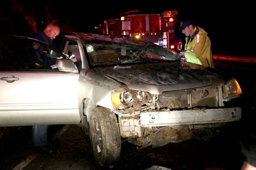 According to CHP Officer Ben Bolon (right), Richard McCleary, 67, of Silverado, was traveling westbound on Highway 74 near mile marker 50 about 7:45 p.m. Friday, Feb. 28, when he lost control and rolled his 2002 Toyota Highlander. American Medical Response transported McCleary, who was complaining of chest pain, to Riverside Regional Medical Center. Bolon and CHP Officer Mike Murawski (left) assess the scene. The cause of the crash is under investigation. Photo by Jenny Kirchner