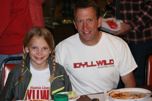 Cross-country runner Brooke Arnson (left) and father/coach Lee Arnson enjoy the spaghetti dinner the American Legion Post 800 hosted Saturday night to raise money for the cross-country team, the Mountain Lions. The teams are composed of children from fifth grade and up. Lee said the team needs money for jerseys and to fund bus travel to the meets in Temecula and Hemet. Grandma and Grandpa Neu organized the dinner and have been avid supporters. Photo by Jay Pentrack