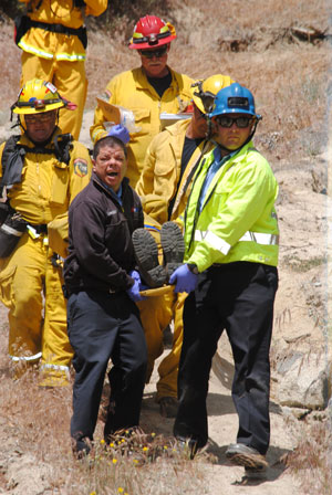 Part of the drill included the report of a down firefighter (left), who had to be found and transported from the fire scene to safety. Photo by J.P. Crumrine.