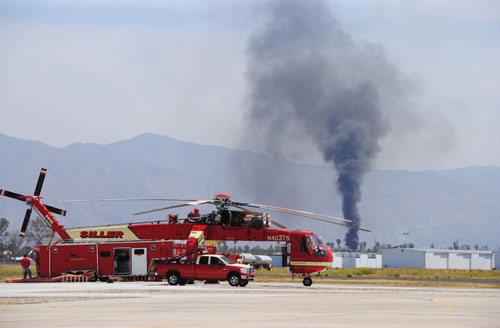 """Last Friday, Cal Fire held the """"Wildfire Awareness Week"""" media day at the Hemet-Ryan Air Attack Base. Ironically, a fire (in the background) began burning just as the event was beginning.             Photo by J.P. Crumrine"""