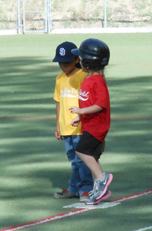 T-ball players from the Padres (in yellow) and the Angels (in red) greet each other on first base. Photo by Teresa Garcia-Lande