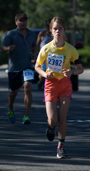 Carmen Pratt, 14, Idyllwild, is the first female runner to cross the finish line in Saturday's Idyllwild 10k Race. Carmen ran the 6.2-mile course in 46:16 minutes. Photo by John Pacheco
