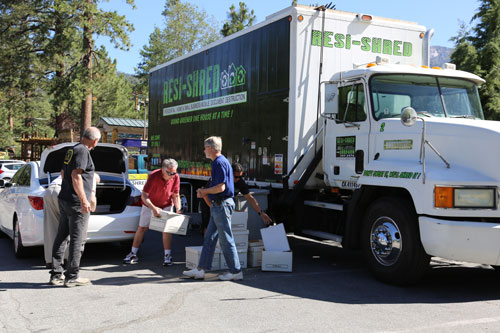 Jim Bilman (left) and Larry Bischof (second from right) help Jim Palmer unload paper to be shredded at Saturday's Shred Fest. Gene Partida (far right) accepts the documents, which are about to be shredded.          Photo by Cheryl Basye