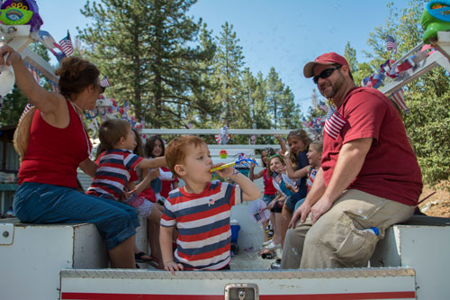 Jackson Carey (center) and father Hal Carey enjoy the Parade from the back of the American Legion Auxiliary float. The annual parade attracts visitors and locals alike.   Photo by John Pacheco
