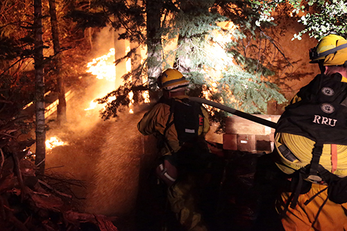 Firefighters head toward the flames, hoses in hand, to put out a debris and vegetation fire Tuesday night in Fern Valley. Photo by Jenny Kirchner