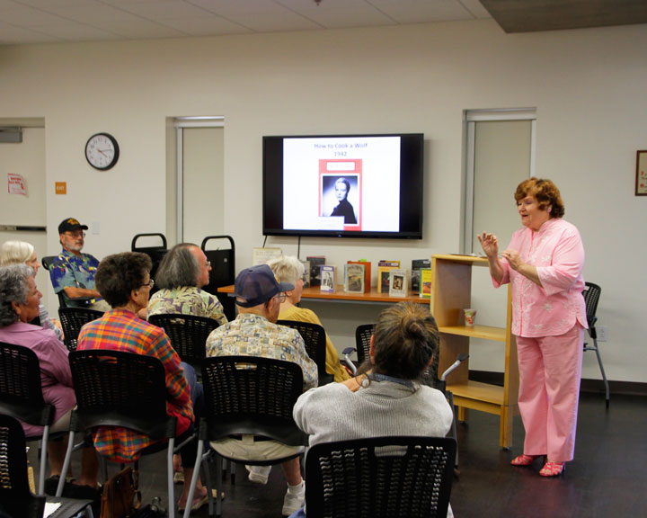 """FISHER TO LIFE: Historical lecturer and Hemet resident Penelope Engard engages the crowd at the Idyllwild Library with stories of late food author MFK Fisher. Fisher once owned 90 acres of land in Hemet with her second husband and authored such books as """"How to Cook a Wolf"""" and """"The Art of Eating."""" Photo by John Drake"""