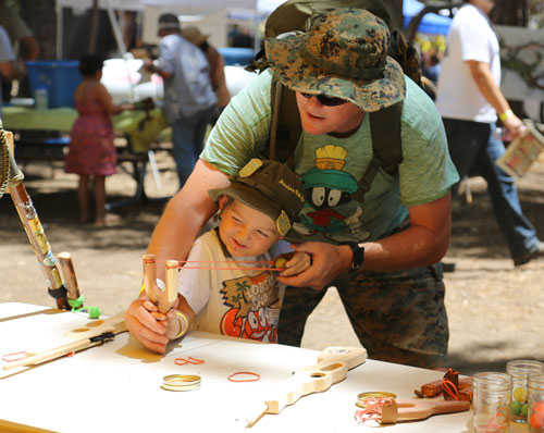 James Wetzel helps his son Luke aim his newly made sling shot at a Pioneer Town activity, which was at the Idyllwild Nature Center during the Fifth Annual Lemon Lily Festival. Photo by Cheryl Basye