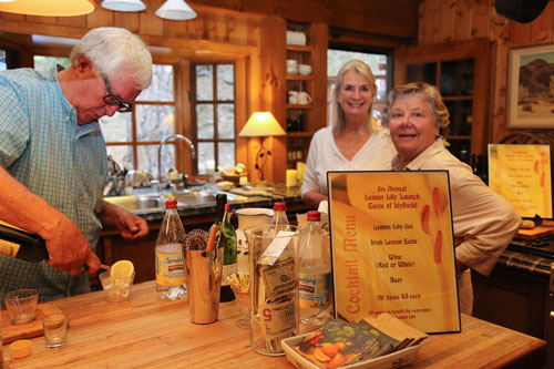 At bottom, Scott Fisher (left), of this year's Lemon Lily Festival committee, prepares a Lemon Lily soda during the Lemon Lily Launch Taste of Idyllwild which Erin O'Neill (center) hosted. Beth Darling (right) watches Fisher's careful bar keeping.  Photo by Cheryl Basye