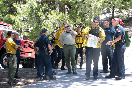 Emergency personnel from Riverside County Fire, the U.S. Forest Service and Idyllwild Fire gather to plan a rescue near the El Guapo Trailhead accessed from Humber Park Sunday afternoon. An adult female climber sustained a fractured ankle and was hoisted by Cal Fire Helicopter 301 and subsequently transported to Keenwild USFS, to be transported to a nearby hospital.  Photo by Jenny Kirchner