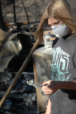 Dylan Fisher studies a piece of melted metal after the Mountain Fire last July that destroyed his family's home. Photo by Marshall Smith