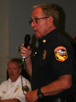 Riverside County/Cal Fire Chief John Hawkins (with Idyllwild Fire Chief Patrick Reitz sitting) talks to the audience at the Fire chiefs meeting on Thursday, June 26, at Town Hall.  Photo by Becky Clark