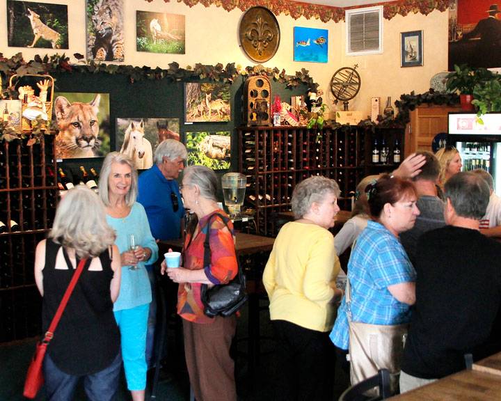 Erin O'Neill and fellow photographer Francoise Frigola enjoy a well-attended opening of O'Neill's photography exhibit Sunday at Idyll Awhile Wine Shoppe & Bistro. Photo by John Drake