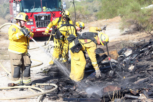 A vegetation fire broke out at Highway 74 and Willowbrook Road Monday in Valle Vista at about 4 p.m., according to a Riverside County Fire incident report. Above, Riverside County Fire fights a small fire, where one outbuilding was destroyed, but the main house threatened was not damaged.  Photo by Jenny Kirchner