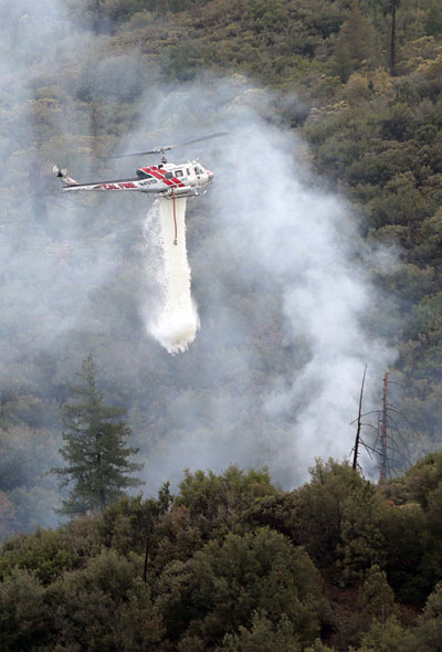 Cal Fire Helicopter 301 drops water on a small lightning fire on Thomas Mountain late Sunday afternoon. Responding units from the U.S. Forest Service and Cal Fire contained the 10-foot by 10-foot fire.       Photo by Jenny Kirchner