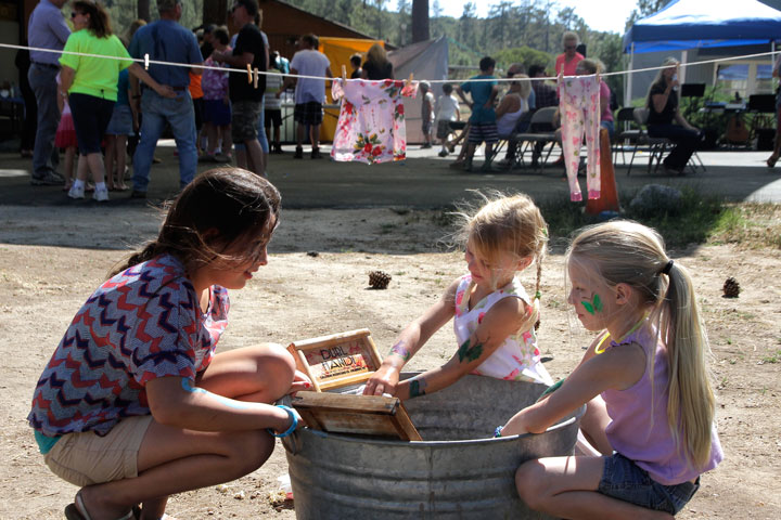 Crossroads Anniversary: Bella Sanchez (left), Joyanna Christina Hale and Miley May play with some old-fashioned washboards at the one-year celebration of the establishment of Chapel in the Pines at Mountain Center last Saturday. The church now calls itself Crossroads 243 Christian Fellowship. Photo by John Drake