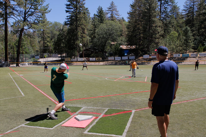 At left, umpire Richard Mozeleski looks on as Idyllwild Arts' Bo Dagnall gets a piece of TJ Titus's pitch to put one into the outfield. IA played Higher Grounds during last Sunday's adult softball games at Idyllwild School. Photo by John Drake
