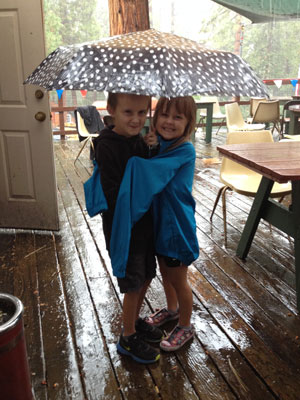 Carter and Evelyn Johnson share an umbrella during the thunderstorm Saturday while enjoying the Sons of the American Legion Post 800 Horseshoe Tournament.  Photo by Halie Wilson