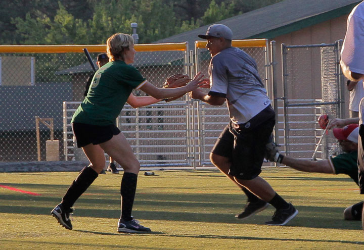 In a pickle, Pitcher Ryan Fish (center) for the Ajax team struggles to get back to first base just before second baseman Bo Dagnall (right) with first baseman and wife Ginger Dagnall get him out during last Thursday's adult coed softball at Idyllwild School.       Photo by John Drake