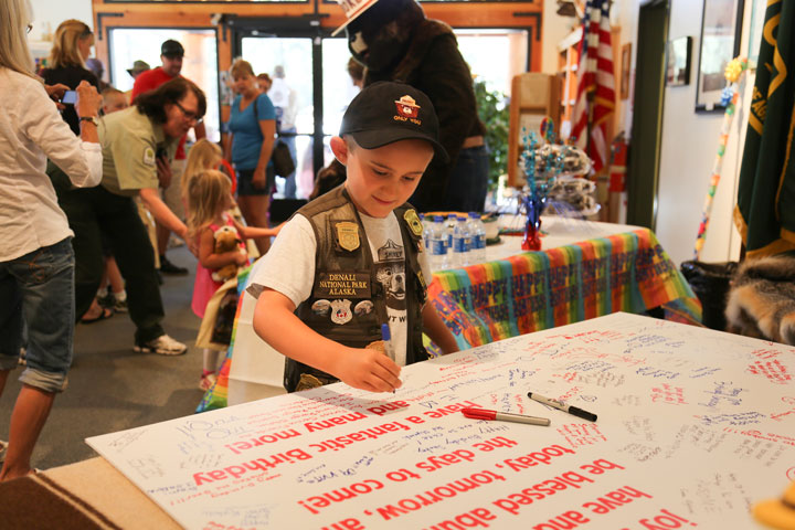 Happy Birthday Smokey: At left, Aug. 9 was Smokey Bear's 70th anniversary and the Idyllwild Ranger Station hosted a birthday party. Cole Daniels makes sure he signs Smokey's birthday card. Photo by Cheryl Basye