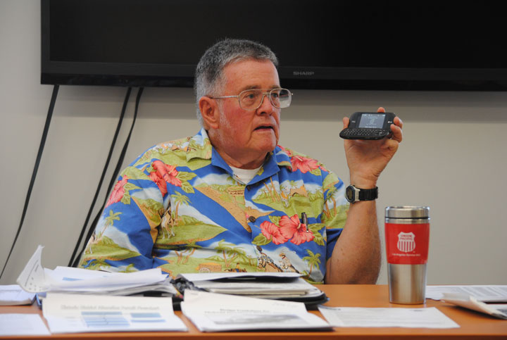 Warren Monroe, chair of the Local Review Board for the Idyllwild Historic Preservation District, holds his phone up for the entire board to hear applicant Paul White discuss his property. Minutes later, White and his wife Katherine arrived at the board meeting in person.  Photo by J P Crumrine