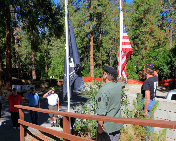 POW SALUTE: Master Sgt. Danny Richardson (lower left), Specialist 4th Class Joe Neu and Warrant Officer David Fraser salute as the colors are lowered to half mast by Master Sgt. Draper (center) and U.S. Marine (ret.) Fred Maholland (right) in remembrance of American POWs and MIAs. This was the first ceremony held by the American Legion Post 800 for this national day of remembrance on the third Friday of September. Photo by John Drake