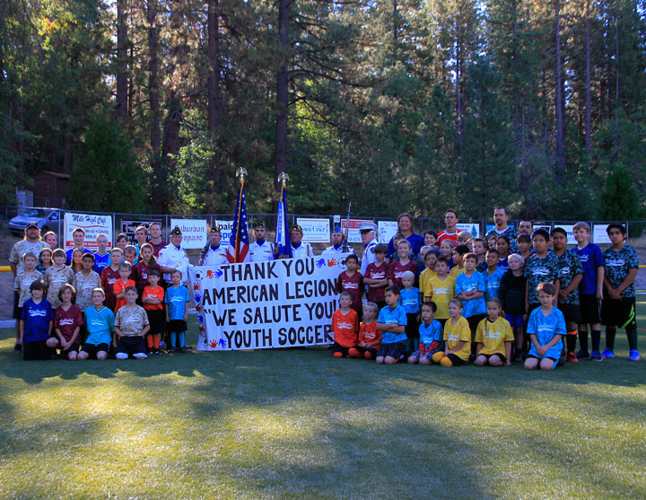 """LEAGUE SHOWS SUPPORT: Coaches, parents and players in the Town Hall Youth Soccer League stand with American Legion Post 800 members to show their support all season with a display of special """"camo"""" jerseys. Photo by John Drake"""