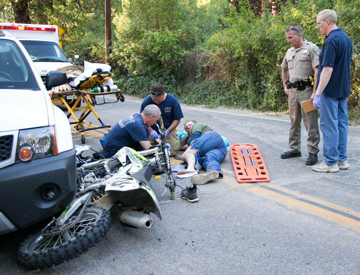 On Friday at about 5:30 p.m., Doug McKellar, 37, of Idyllwild, (on the ground) was traveling on South Circle when he lost control of his motorcycle while taking a right onto Village Center Drive, according to CHP Officer Chris Blondon. He slid under a white 2012 Nissan Xterra driven by Wayne Sleme, of Idyllwild, who was traveling toward South Circle. McKellar suffered a compound fracture to his left leg and was transported by Idyllwild Fire to Desert Regional Medical Center. Sleme was uninjured. Photo by Jenny Kirchner.