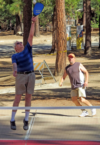 Ron Perry leaps high to volley during a pickle ball game Sunday morning. Photo by Doris Lombard