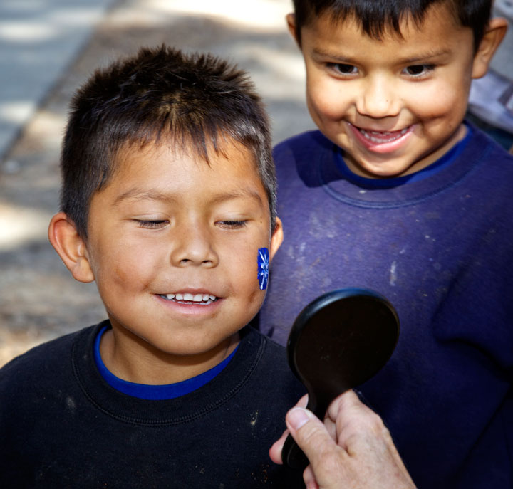 Xavier Diaz gets his face painted as brother Moises looks on during Acorn Day at the Nature Center 2014.          Photo by Gina Genis
