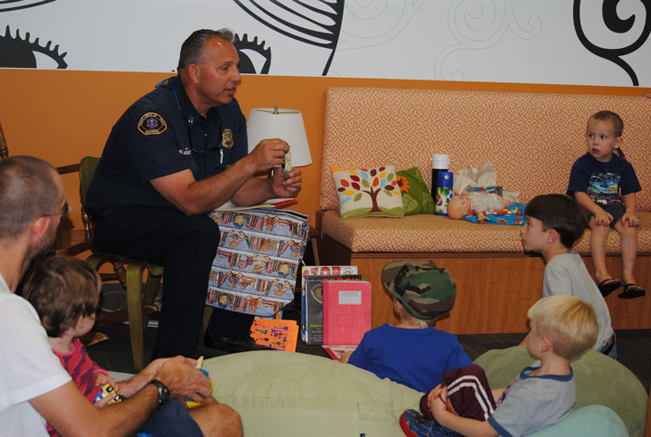 During fire prevention week, an Idyllwild Fire Department crew visited the Idyllwild Library during story time to discuss fire prevention. Here, Capt. Mark LaMont talks about being safe near electrical outlets.       Photo by J.P. Crumrine