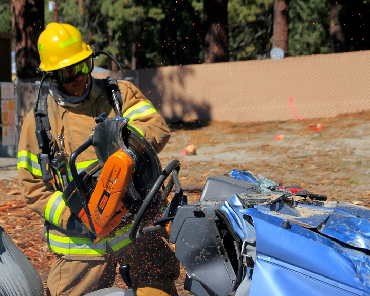 IFPD OPEN HOUSE: Idyllwild Firefighter Nelson Escobar saws at the steering wheel demonstrating life-saving equipment at the Idyllwild Fire Department's open house Saturday.                                            Photo by John Drake