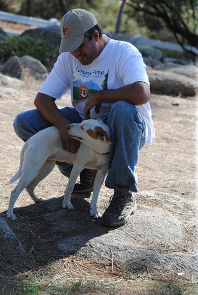 """Living Free Kennel Manager Edgar Santiago pets Jazz, one of many dogs for adoption at the Oct. 25 """"Bluegrass Howl and Yowl.""""      Photo by J.P. Crumrine"""