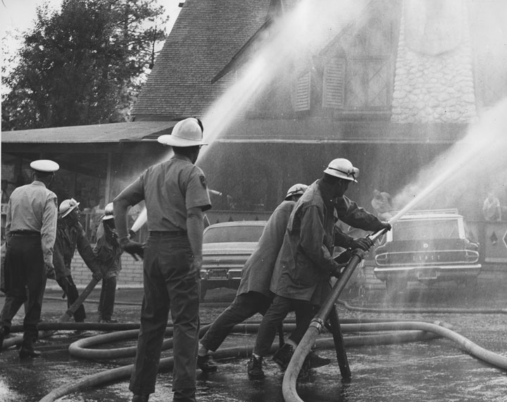 Idyllwild Firemen demonstrate water pressure at Fern Valley Corners in the early 1960s. The building now houses the Creekstone Inn.             File photo