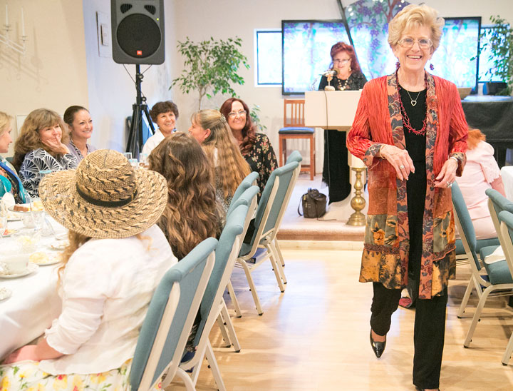 TEA & FASHION: Sunday afternoon, Marion Young (right) models an outfit during the High Tea and Fashion Show fundraiser for the Spiritual Living Center, which was sponsored by Prairie Dove. Phyllis Brown, owner of Prairie Dove, is shown at the podium.        Photo by Jenny Kirchner