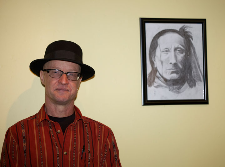 Andrew Jones with his American Indian drawings on exhibit at the Town Baker last Saturday during an artist reception.         Photo by Gina Genis